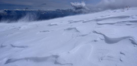 強風吹き荒れるシュカブラの雪原と南アルプス