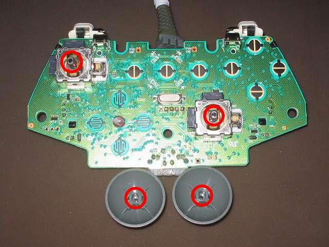 シリコンコントローラーカバー装着済み Xbox 360 コントローラーとカバー付きアナログスティックの干渉トラブル スティックコントローラーの軸(画像上側赤丸 2ヶ所)とアナログスティック軸差し込み穴(画像下側 2ヶ所)の間に詰め物を入れて高さを調節改造する