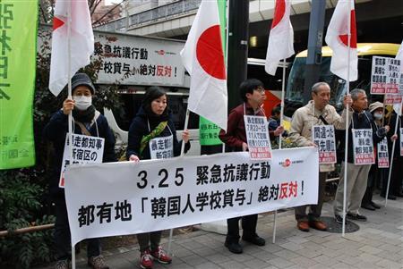 東京都が都有地を韓国学校の増設用地として貸与することに「絶対反対」のプラカードを掲げ声を上げる人たち=25日午後、東京都新宿区の都庁前