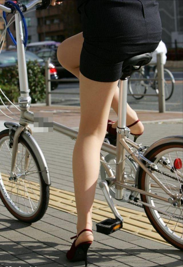 タイトスカートのスーツを着て自転車に乗る女