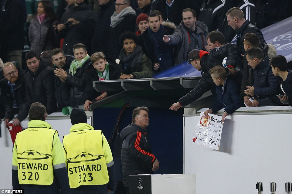 Van Gaal is confronted by some spectators as he leaves the pitch at the Volkswagen Arena