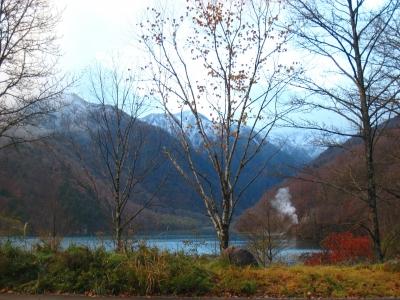 エメラルドグリーンの湖水と秋色の麓