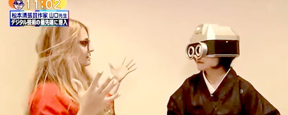 ワイドナショー画像 触れ合いを具現化したカメラをかぶって体験する山口恵以子と説明係の外国人 2015年11月8日