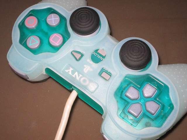プレイステーション デュアルショックシリーズ (PlayStation DUALSHOCK) シリコンコントローラーカバー ホワイト 装着後のデュアルショック SCPH-110 エメラルド コントローラー中央部分撮影、ANALOG ボタンの一部シリコンカバー接触、シリコンカバーとコントローラーの間に隙間あり、デュアルショック 3 のアナログスティックと比べ高さが低いため一部シリコンカバーとキャップ付アナログスティックとの接触あり