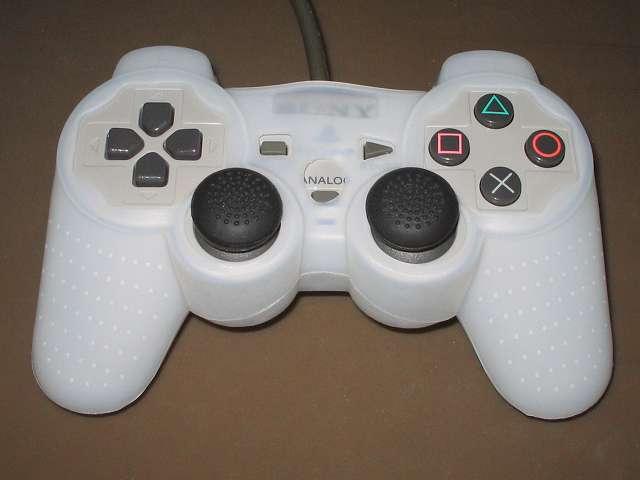 プレイステーション デュアルショックシリーズ (PlayStation DUALSHOCK) シリコンコントローラーカバー ホワイト 装着後のデュアルショック SCPH-1200 コントローラー ボタン・スティック側表面、ANALOG ボタンの一部シリコンカバー接触、シリコンカバーとコントローラーの間に隙間あり、デュアルショック 3 のアナログスティックと比べ高さが低いため一部シリコンカバーとキャップ付アナログスティックとの接触あり