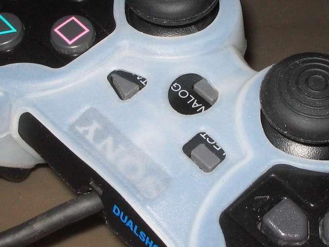 プレイステーション デュアルショックシリーズ (PlayStation DUALSHOCK) シリコンコントローラーカバー ホワイト 装着後のデュアルショック 2 SCPH-10010 コントローラー中央部分拡大撮影、ANALOG ボタンとシリコンカバーの穴の位置にズレあり、シリコンカバーとコントローラーの間にやや大きな隙間あり、デュアルショック 3 のアナログスティックと比べ、スティック部分の高さが低いためか、キャップ付アナログスティックとシリコンカバーとの接触あり
