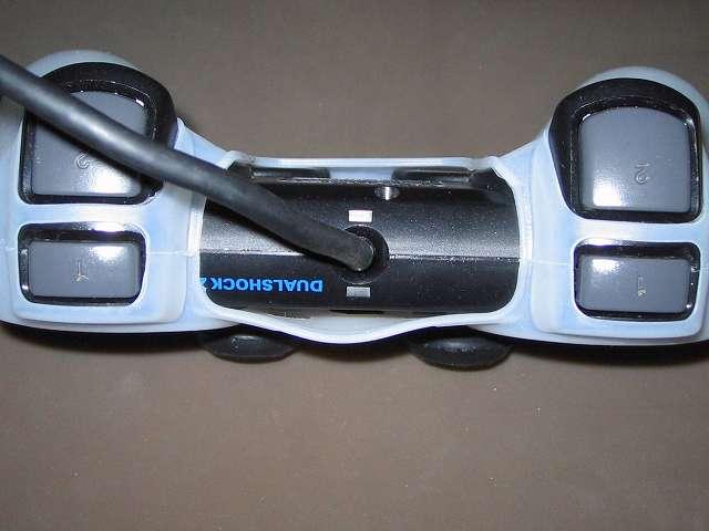 プレイステーション デュアルショックシリーズ (PlayStation DUALSHOCK) シリコンコントローラーカバー ホワイト 装着後のデュアルショック 2 SCPH-10010 コントローラー ケーブル根本側から撮影、シリコンカバー装着後のコントローラー中央表面と裏面の隙間状態